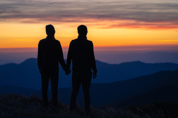 The silhouette of the couple on the mountain with a sunset background