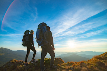 The couple standing on the mountain with a picturesque sunrise background