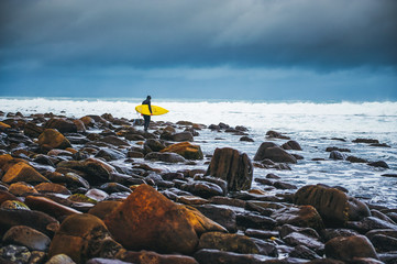 Surfer walking on the rocks towards the ocean