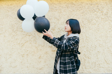 Asian young woman with balloon on city street