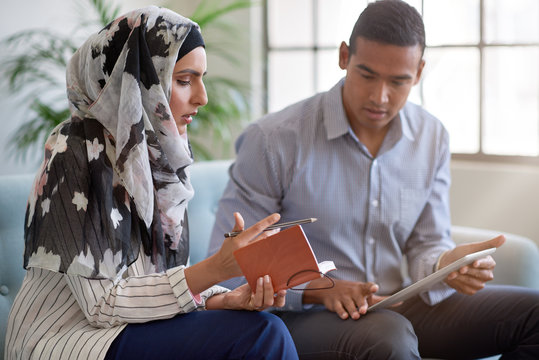 Businesswoman in headscarf having serious discussion