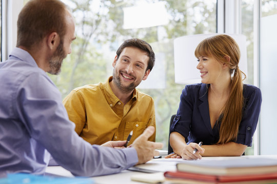 Couple Listening To Advisor Discussing In Office