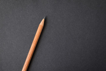 Top view of notebook black cover with wood texture pencil on white desk background