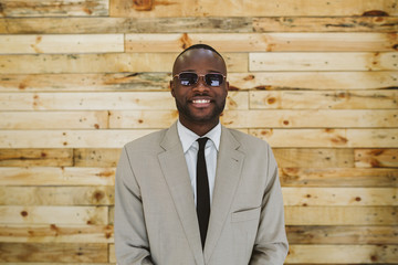 Portrait of a young african businessman with sunglasses over a w