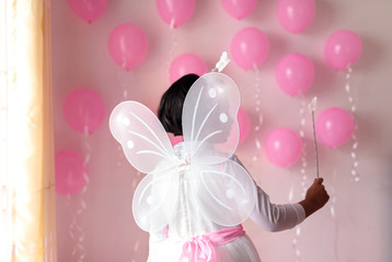 Little girl on her birthday dressed with butterfly wings holding magic stick