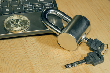 The problem of security of electronic money. Bitcoin gold coin on netbook and padlock with keys on wooden table.