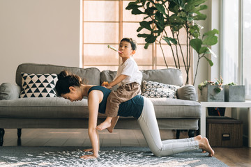 Adorable boy doing yoga with his mother