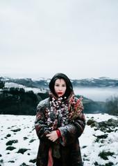 portrait of a beautiful woman wearing a fur coat in a winter landscape