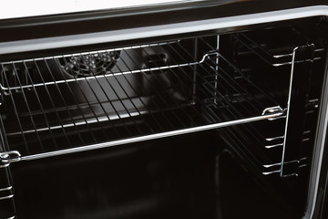 Open empty electric oven with rack, closeup
