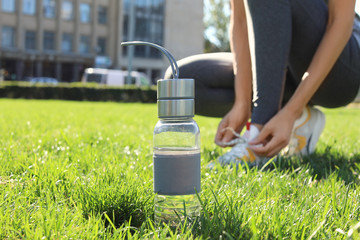 Bottle with water near woman lacing her sneakers outdoors