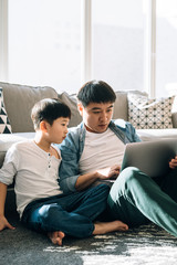 Boy and dad use laptop at home