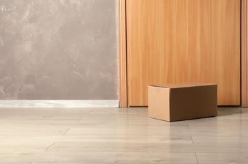 Cardboard box on floor near apartment entrance. Mockup for design