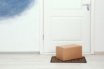 Cardboard box on floor near apartment entrance. Mockup for design