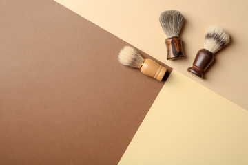 Flat lay composition with men's shaving brushes and space for text on color background