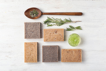 Flat lay composition with handmade soap bars and ingredients on white wooden background