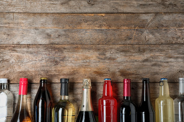 Obraz Bottles with different alcoholic drinks on wooden background, top view. Space for text - fototapety do salonu