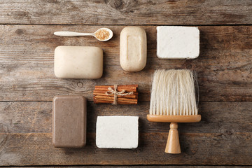 Wall Mural - Flat lay composition with different soap bars on wooden background