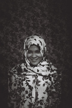 Happy beautiful muslim girl in floral pattern hijab on flower prints shirt and ditsy background