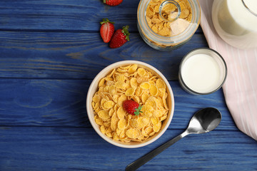 Flat lay composition with healthy cornflakes in bowl on wooden table