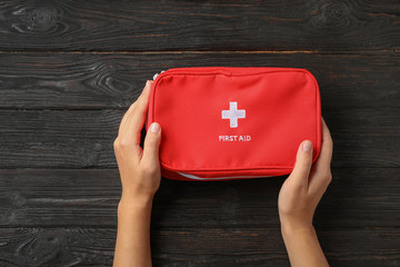 Woman holding first aid kit on dark table, top view