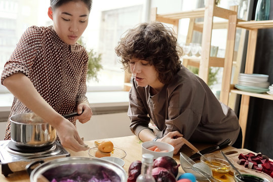 Female friends dyeing Easter eggs