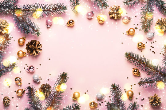 Pastel Pink Christmas Background. Festive frame of fir branches, toys and golden bokeh lights