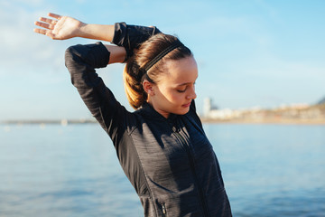 Young woman stretching on the beach.