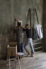Young couple hanging a frame on the wall in new house