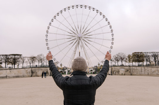 Person posing with observation wheel