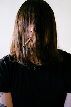 A caucasian man smoking a joint