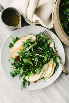 Overhead view of pear and arugula salad with champagne dijon vinaigrette