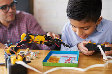 Boy teaching himself how to use a science kit robot
