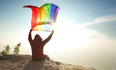 man sitting on mountain top raise rainbow LGBT symbol flag to bright sunny blue sky