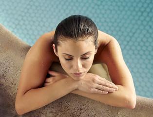 Hispanic woman relaxing in swimming pool at luxury resort