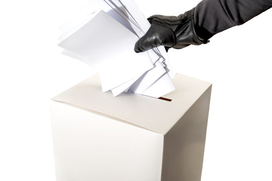 Electoral fraud and hacked elections concept with a hand wearing a leather glove and stuffing a ballot box isolated on white background with copy space and a clip path cutout