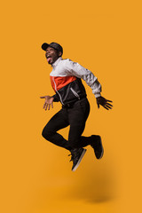 Stylish sporty man jumping over a yellow background