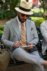 Stylish man with hat and suit using a tablet