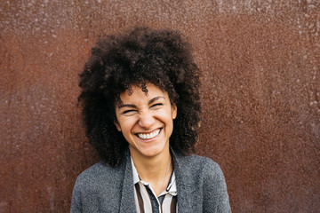 Funny laughing woman with afro hairstyle.