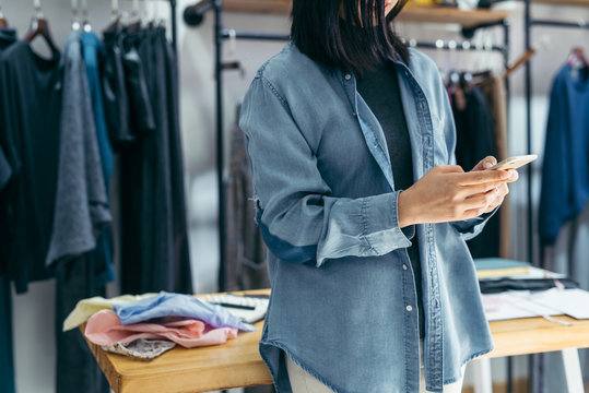 Business owner using smartphone in clothing store