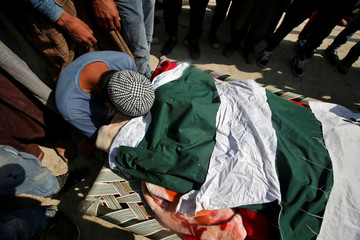 A man mourns over the body of Shabir Ahmad Dar, a suspected militant, who according to local media was killed in a gunbattle with Indian security forces, during his funeral in Samboora