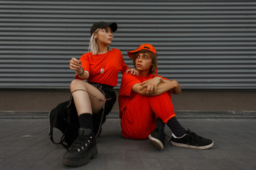 Fashionable beautiful stylish young couple with caps in fashionable orange clothes with fashion shoes are sitting on the street near the metal gray wall Wall mural
