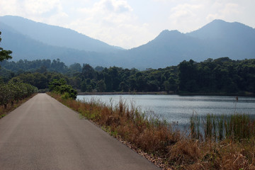 View of a straight road running past a lake with the mountains of Khao Soi Dow District of Thailand in the background.