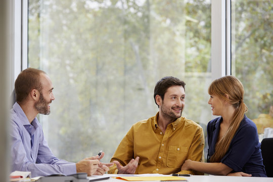 Smiling Couple Consulting With Advisor In Office
