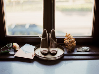 Elegant wedding details: a vintage tray, rings, invitations and a pair of wedding shoes