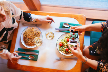 Overhead of female friends eating in restaurant.