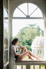 Elegant woman sitting on window sill