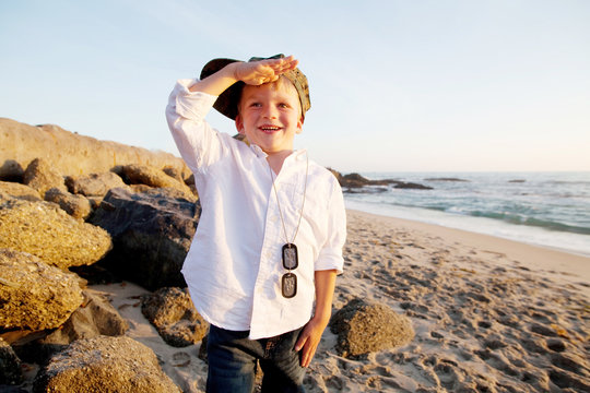 Young Boy At Beach Wearing Military Tags And Saluting