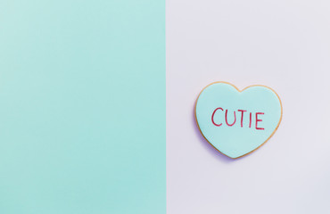 pale valentine candy cookies with messages over pastel background