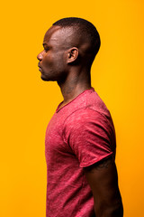 Profile portrait of young black man over a yellow background