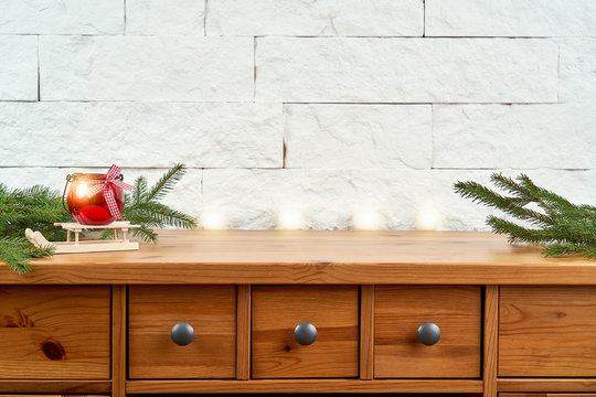 Christmas decoration with twigs of spruce and a red lantern on an old shelf on the background of a white brick wall